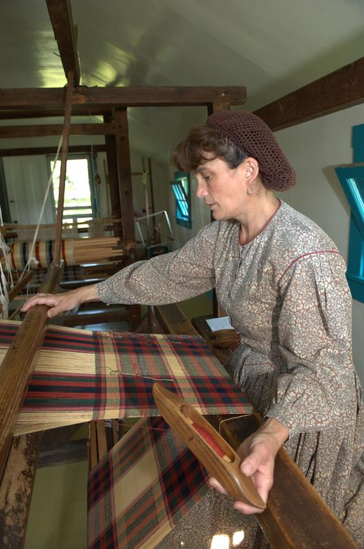 Weaver in historical dress working at a loom